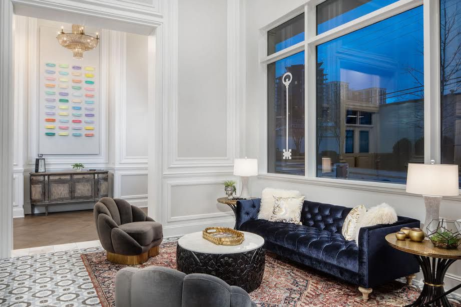 A huge white lobby area with a blue couch.
