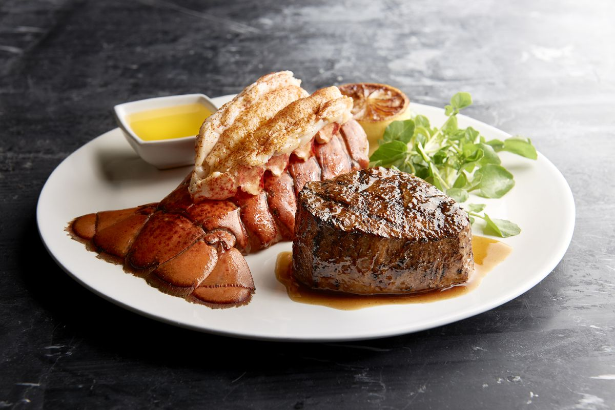 A filet mignon and lobster tail sit on a white plate with butter, lemon, and greens, isolated on a gray background