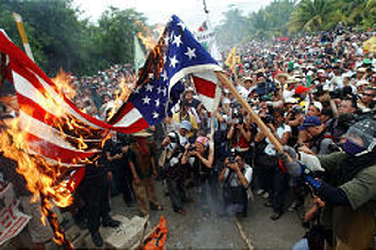 WTO protesters burn a U.S. flag Saturday outside the World Trade Organization meeting in Cancun, Mexico.
