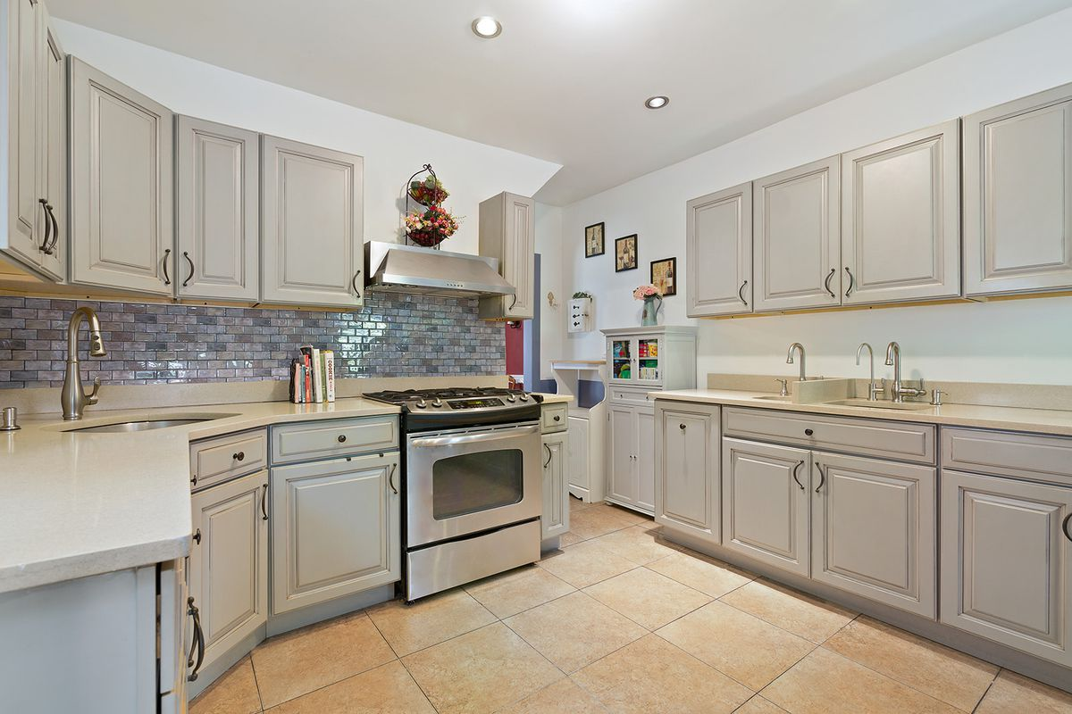 A kitchen with grey wood cabinetry.