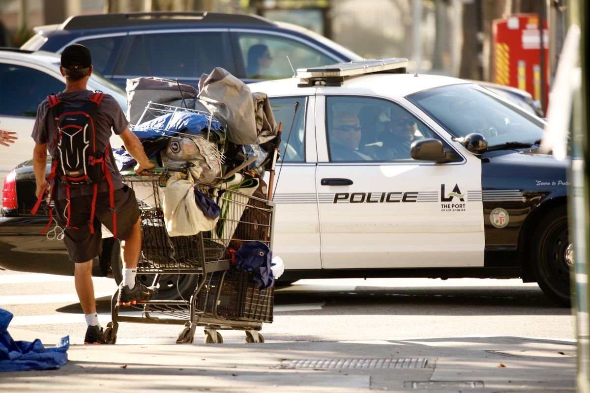 A ban with a backpack pushes a cart full of belongings down a street. A police car is present in the background.