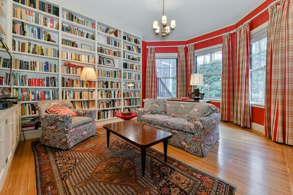 A sitting room with at least two chairs and a large set of built-in shelves filled with books.