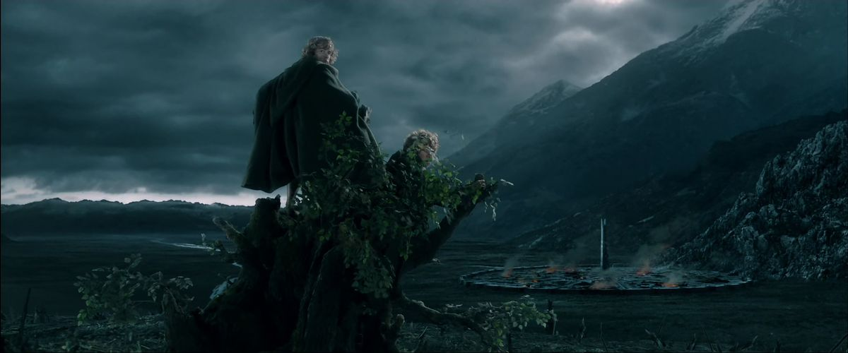Sitting on top of Treebeard, Merry and Pippin survey the fires and smoke of the tower of Orthanc at Isengard in The Two Towers.