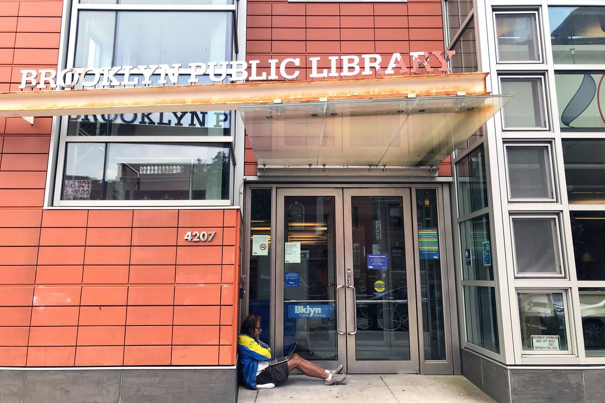 A man uses the free WiFi for a morning conference on his computer in front of the library on 18th Avenue in Kensington, Brooklyn, Sept. 11, 2020.