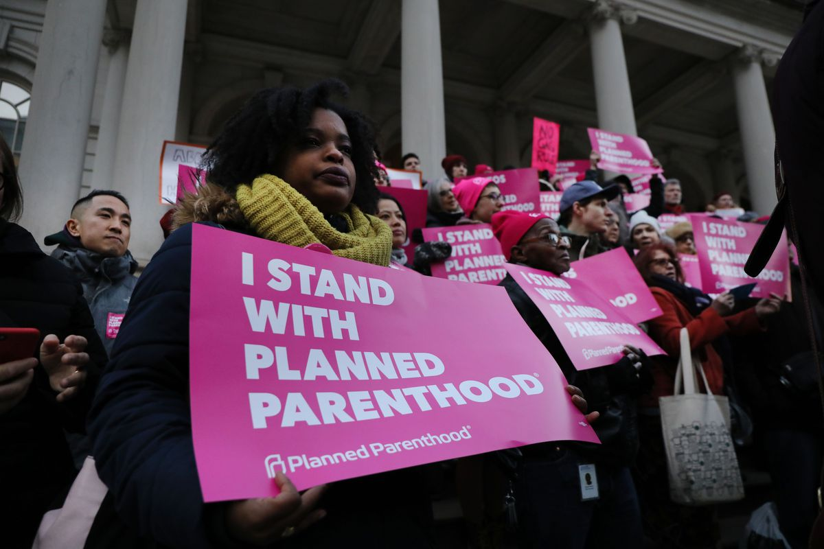 "Supporters of Planned Parenthood hold pink signs, one reading ""I stand with Planned Parenthood."""