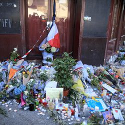 Olive branches were among the foliage left in front of the restaurant by mourners