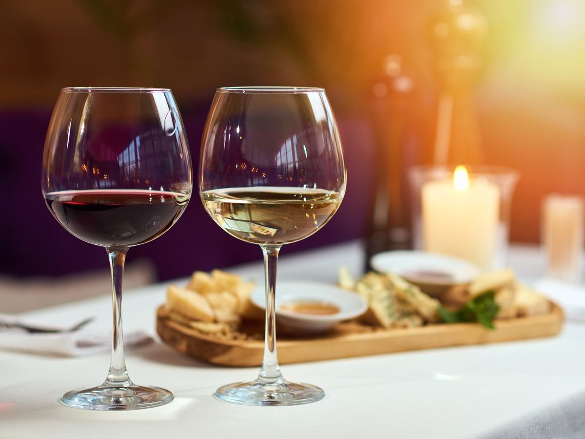 Two glasses of wine white and red standing on a table with a platter of cheeses and candle behind them in the sun light