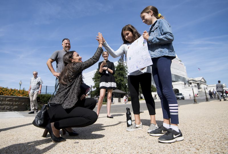 Representative Alexandria Ocasio-Cortez squats down to give a high five to a couple of students at the Global Climate Strike in Washington, DC