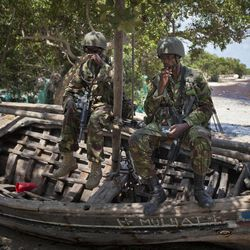 FILE - In this Wednesday, Dec. 14, 2011 file photo, Kenyan army soldiers sit on a currently unused fishing boat on the white sand shore of the seaside town of Bur Garbo, Somalia. Kenya's military said Friday, Sept. 28, 2012 that its troops attacked Kismayo, the last remaining port city held by al-Qaida-linked al-Shabab insurgents in Somalia, during an overnight attack involving a beach landing.