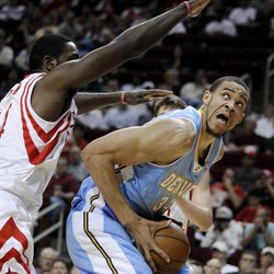 Denver Nuggets' JaVale McGee, right, is guarded by Houston Rockets' Patrick Patterson (54) during the first half of an NBA basketball game Monday, April 16, 2012, in Houston.