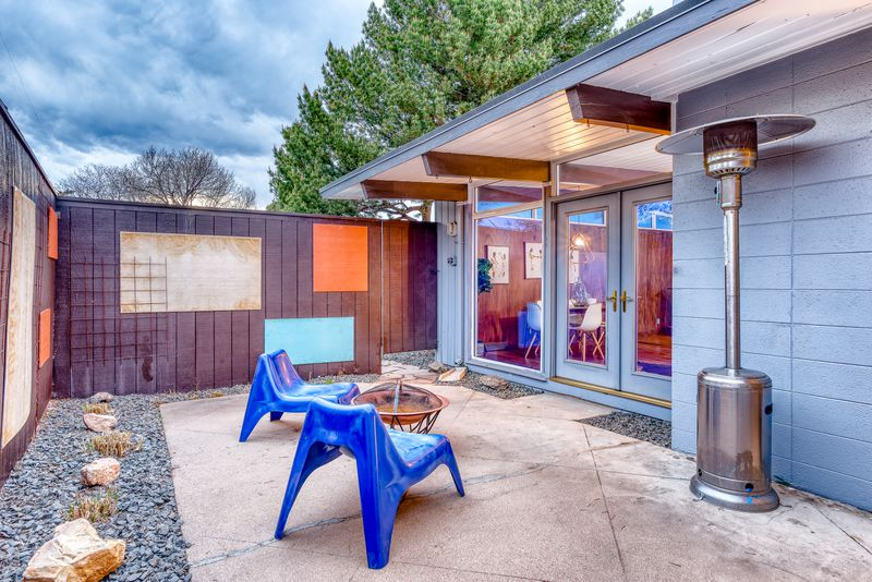 A courtyard has two blue chairs, a fire pit, a heater, and midcentury art on the walls.