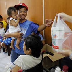 Jeric Walter Apa holds his brother Seandominic Apa as they receive prescriptions in Cebu, Saturday, Nov. 23, 2013. They lost their home in a typhoon.