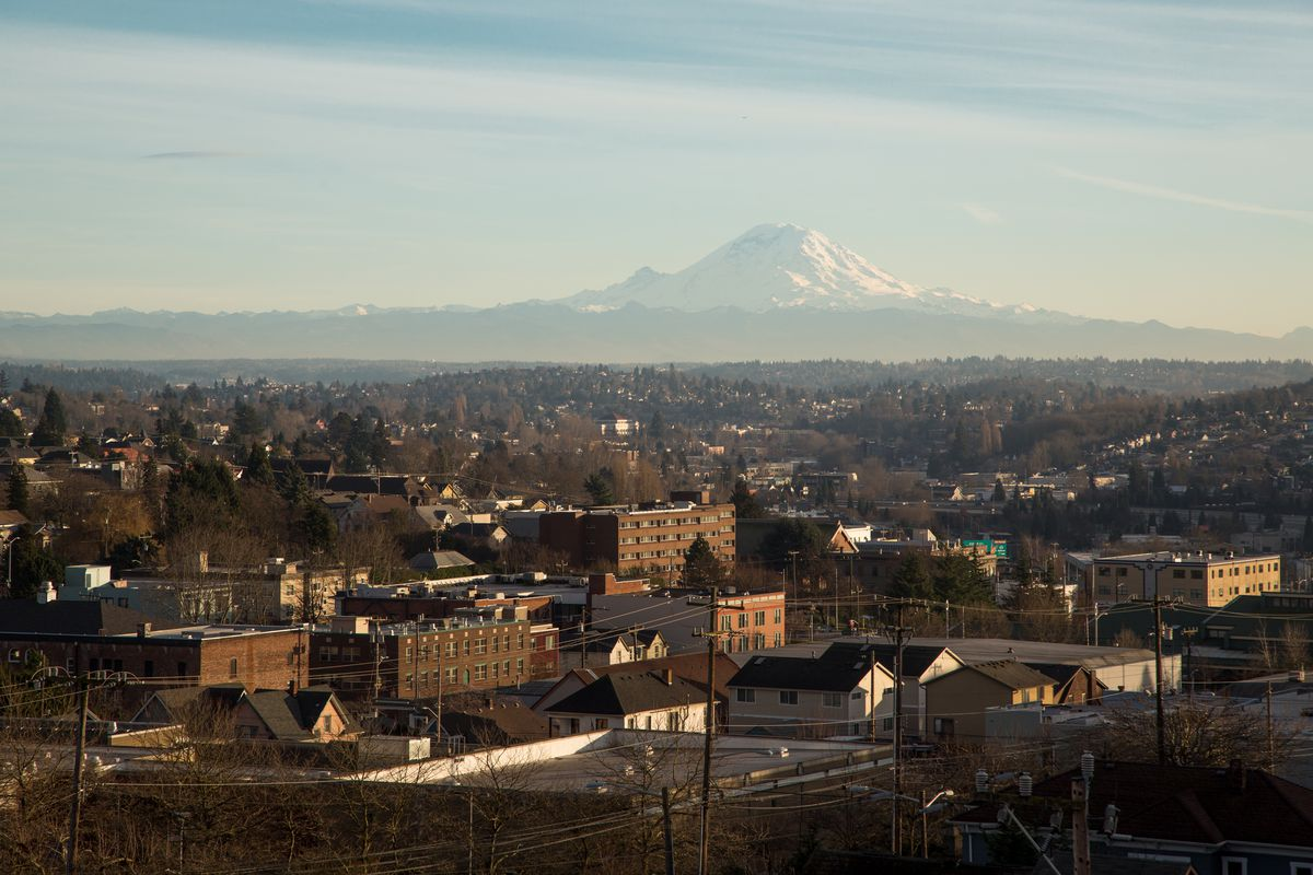 A collection of apartment buildings with a view of Mt Rainier above them
