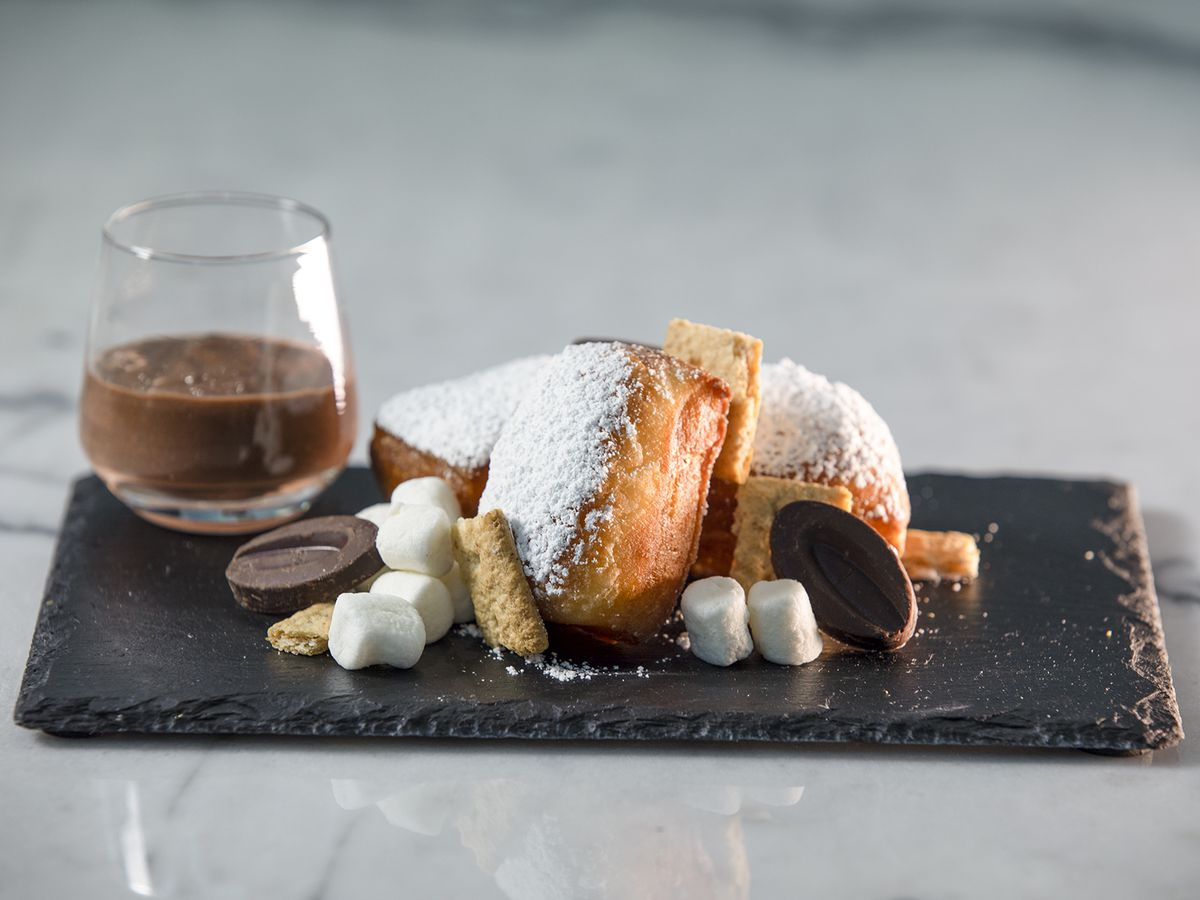 A black plate with espresso and beignets