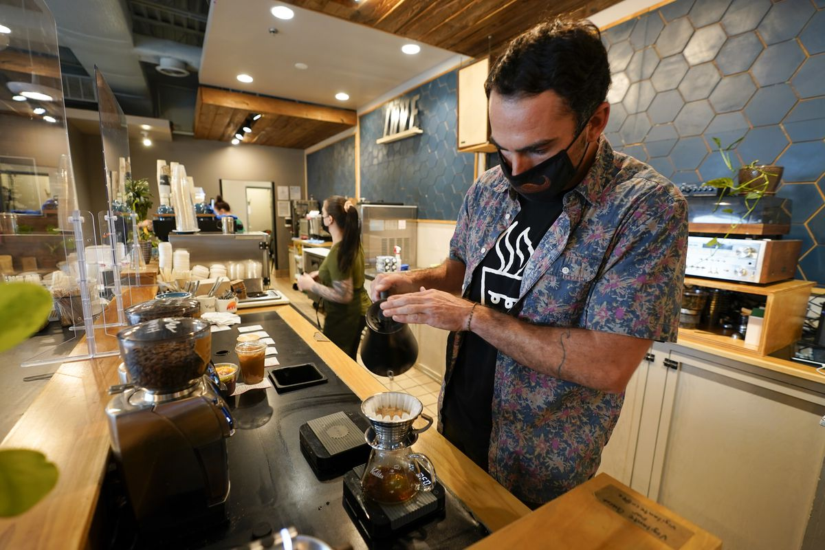 Chris Vigilante makes a dripped coffee for a customer at one of his coffee shops n College Park, Maryland.