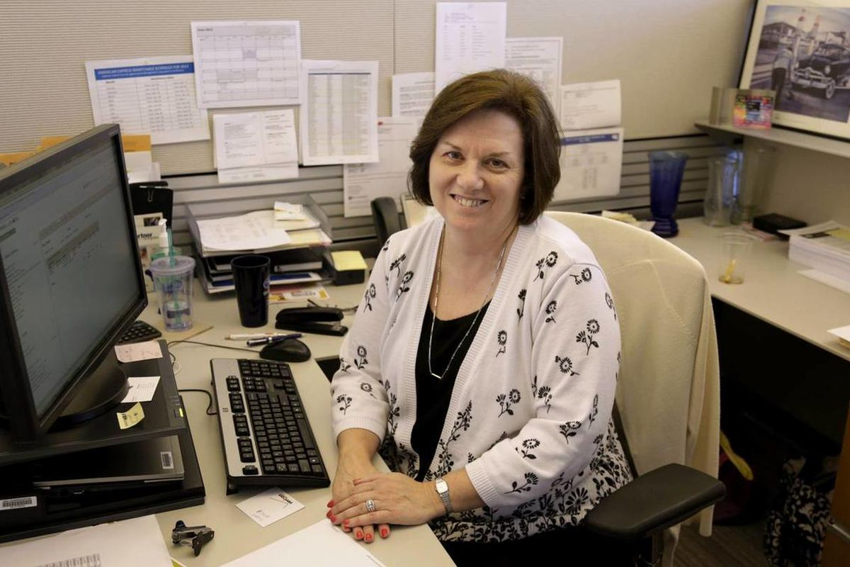 In this June 3, 2013, photo, Nora Kouba, an employee at USG Corporation sits at her work station in Chicago. Over the years, Kouba has made use of a benefit offered by USG that allows their workers to buy and sell vacation time, a perk that gives workers
