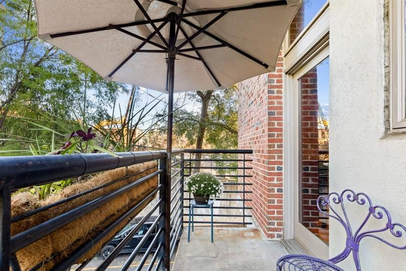 A long patio space with a purple chair and black railings.