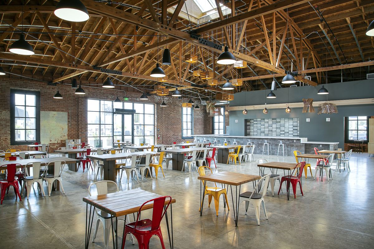 A tall-ceilinged warehouse building repurposed as a food hall.