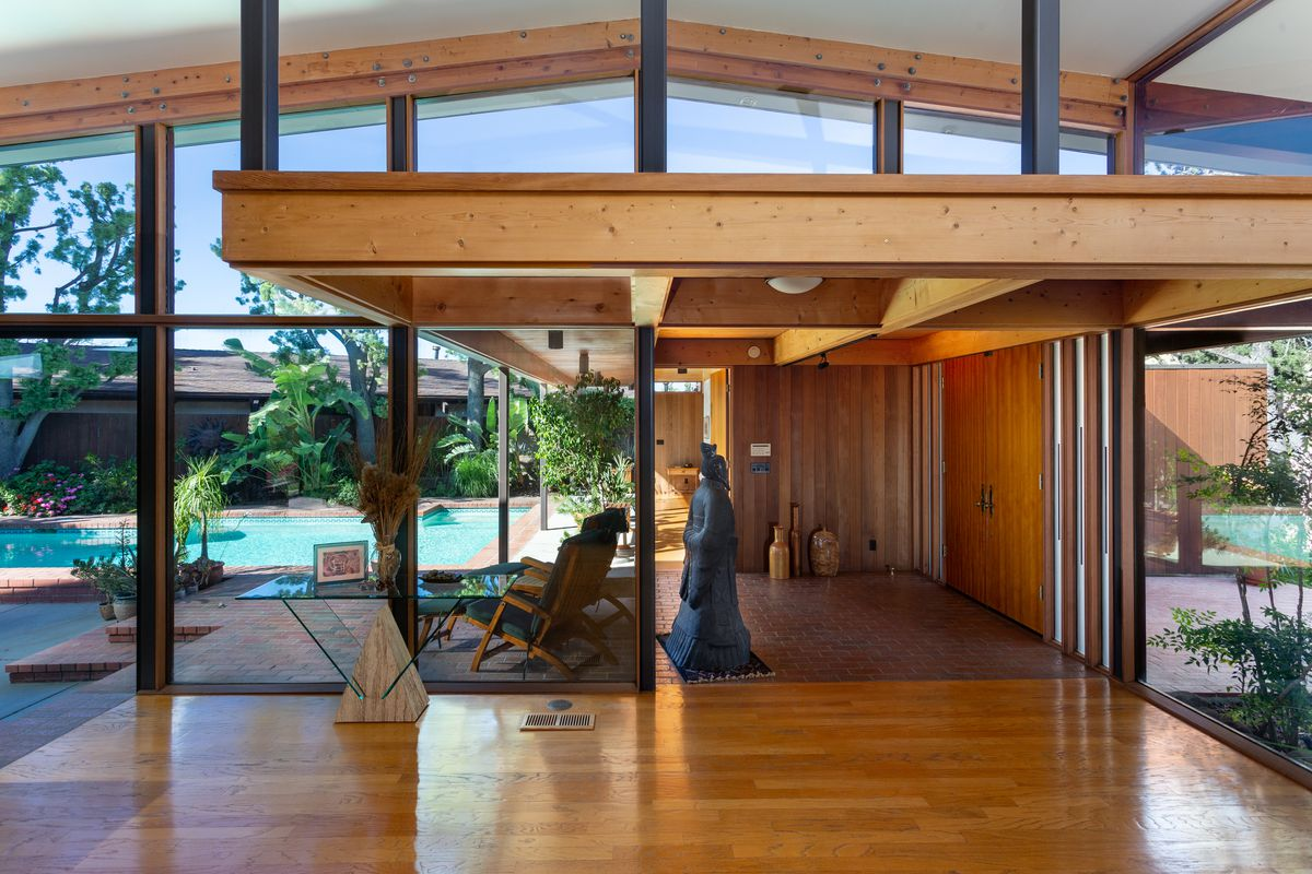 Airy space with wooden floors and glass walls overlooking a pool.