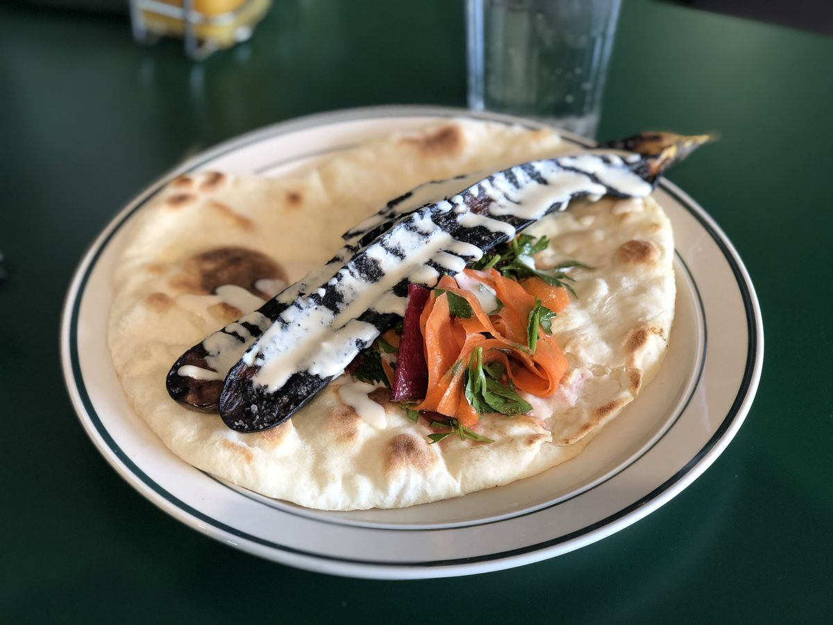 Sliced and charred eggplant sits on flatbread next to a pile of thinly sliced carrot, beets, and cilantro with white sauce drizzled on top.
