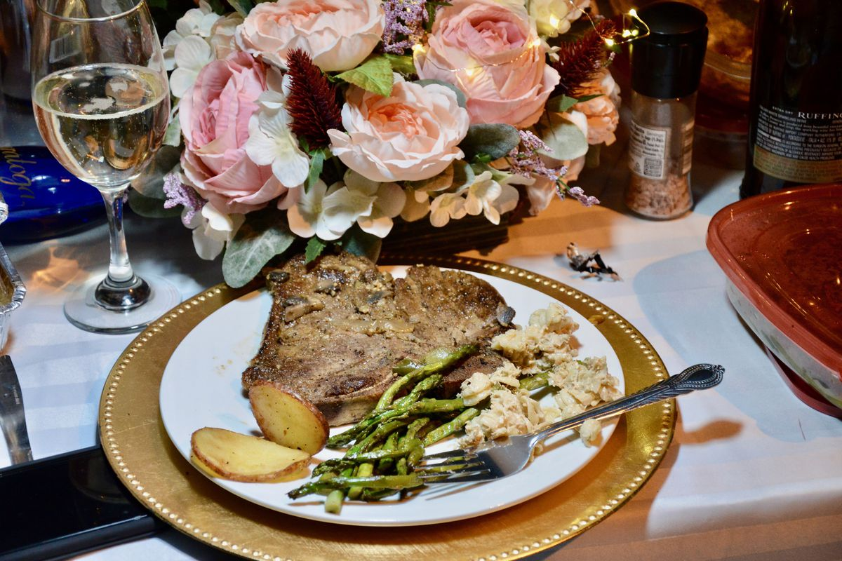 flowers behind plate of steak, beans, and potatoes