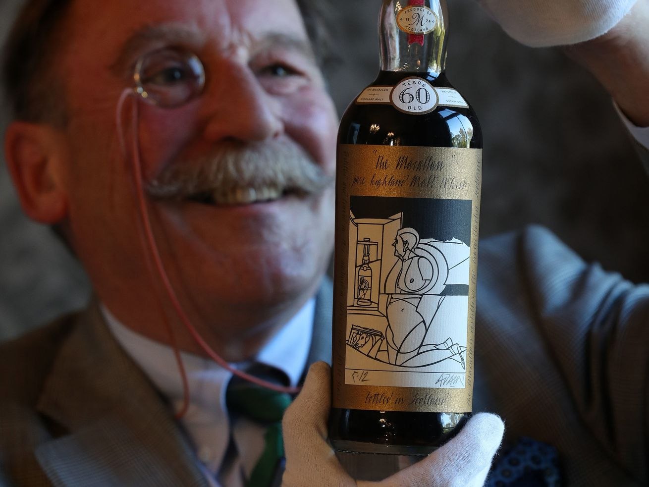 Whisky expert Charles MacLean inspects a bottle of Macallan Valerio Adami 60-year-old 1926, which sold for a record-breaking $1.1 million at auction last week.