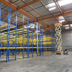 """A worker on an <a href=""""http://www.elcheapolifts.com/"""">El Cheapo Lift</a> inspects lighting."""
