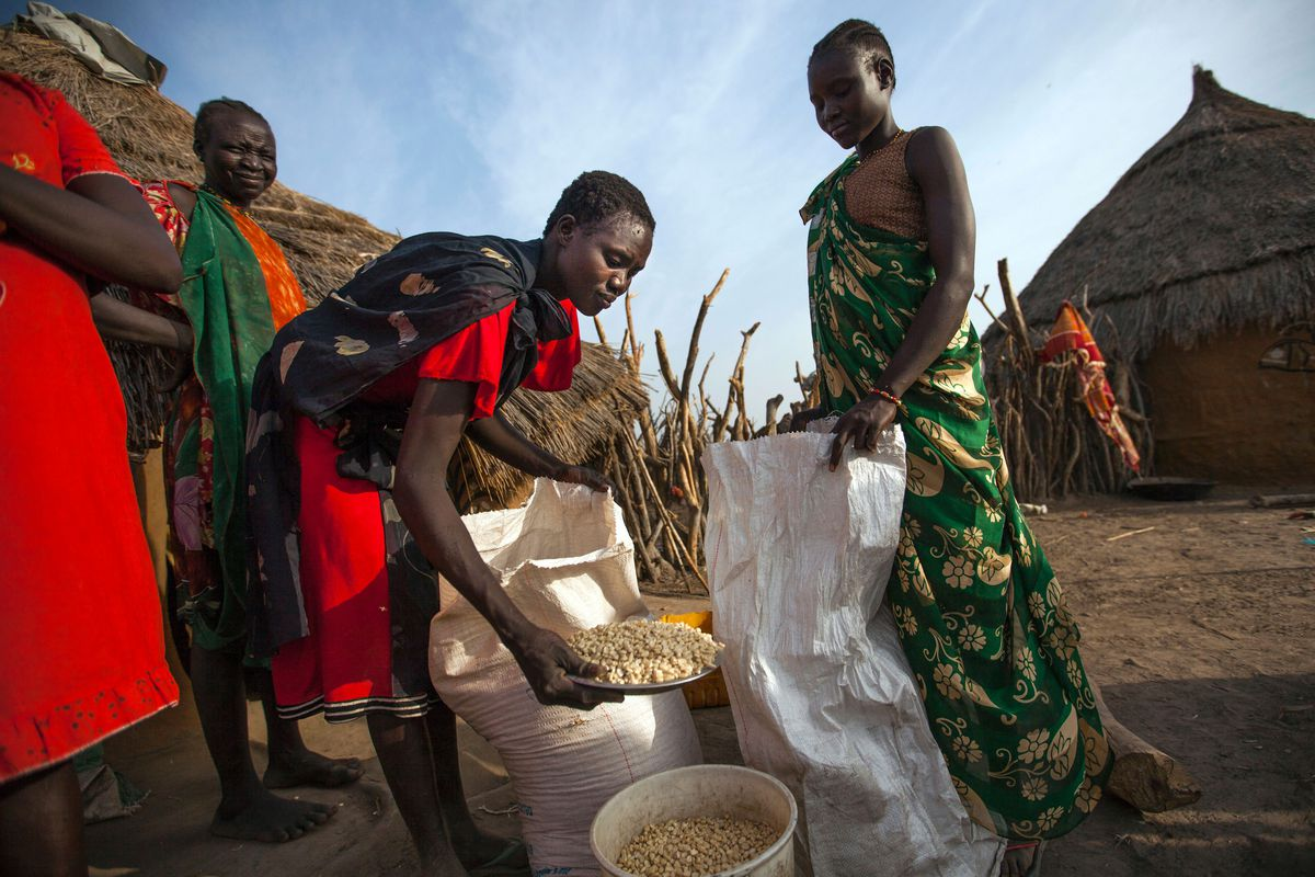 Three woman gather around a bag of maize and one scoops maize into her bag using a bowl.