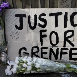 A poster and flowers are left near Grenfell Tower in London, Saturday, June 17, 2017. Police Commander Stuart Cundy said Saturday it will take weeks or longer to recover and identify all the dead in the public housing block that was devastated by a fire early Wednesday.