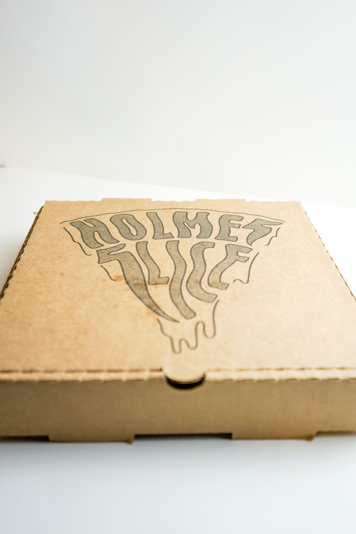 Closed carryout pizza box with the Holmes Slice logo forming a pizza slice, the word Slice is made to look like the letters are dripping down like cheese