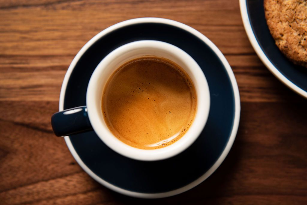 An overhead shot of a black and white saucer and espresso cup filled with caramel-colored espresso set on a wooden table with a corner of a cookie in the upper right side of the frame.