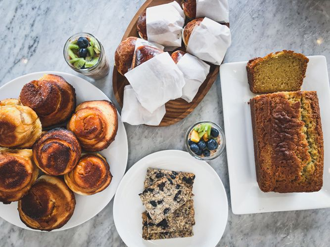 From above, a marble table laden with rolls, bread loaf, sandwiches, and sweet treats