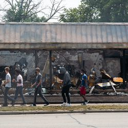 People pass by what used to be B&L Office Furniture, Tuesday afternoon, Aug. 25, 2020. The store was set on fire following the shooting of Jacob Blake by a police officer in Kenosha Sunday.