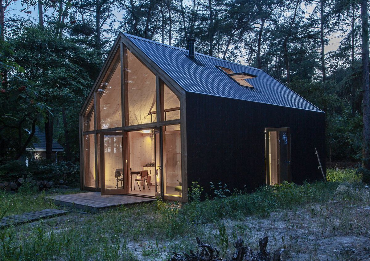 Cabin clad in black, shown lit up from the inside.