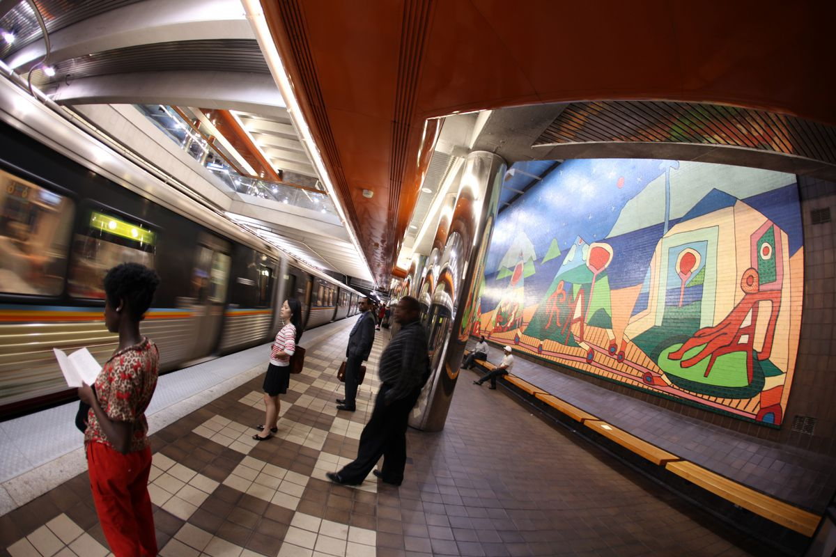 People standing in front of artwork in MARTA station.