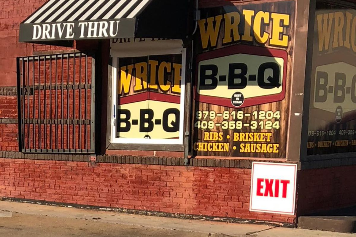 The exterior of a brick building, featuring a drive thru window and signs that read Wrice BBQ