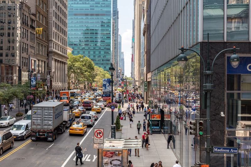 A crowded street in a large city, with trucks, cars, and pedestrians stuck in traffic.