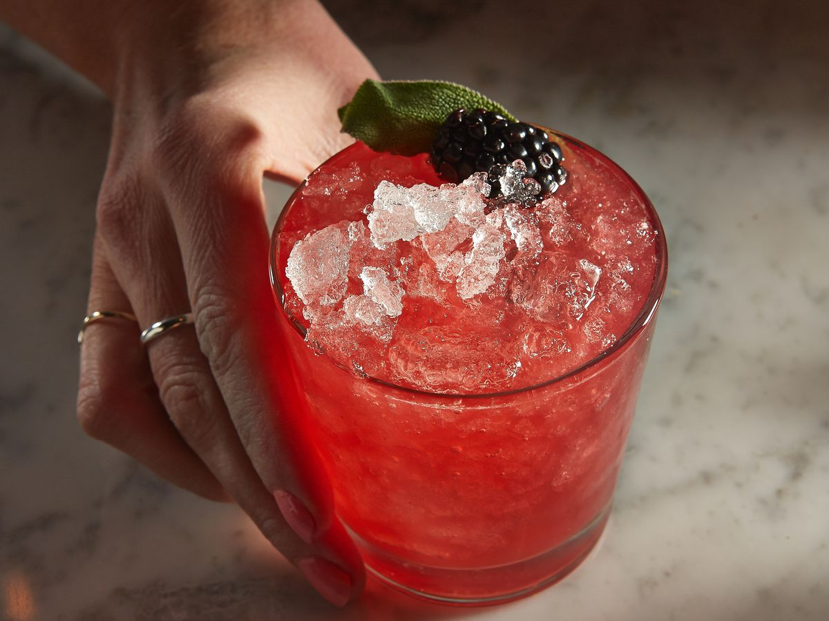 a pink cocktail with ice and a berry garnish