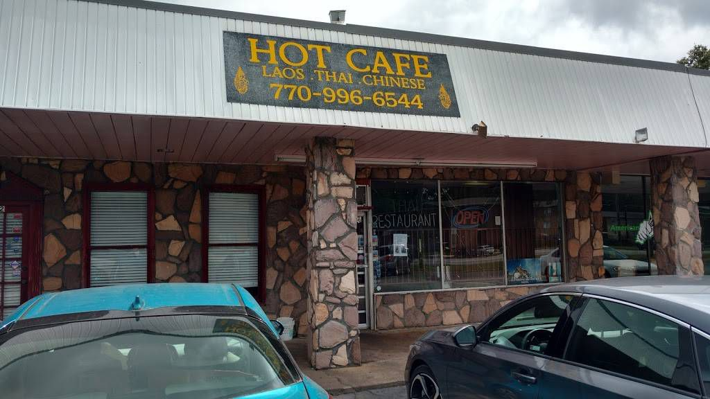 The exterior of Hot Cafe Lao Thai restaurant in Riverdale, GA with two parked cars out front