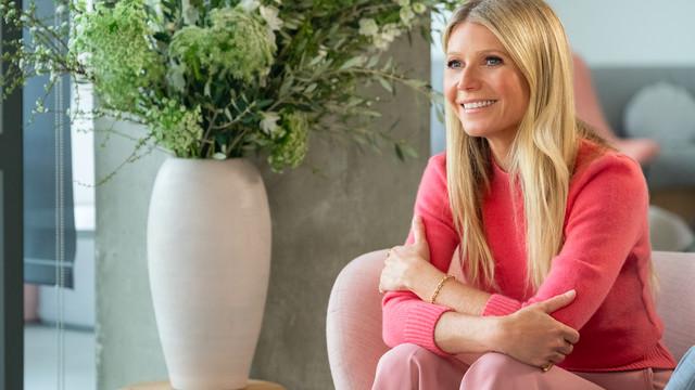 Gwyneth Paltrow sits on a couch.