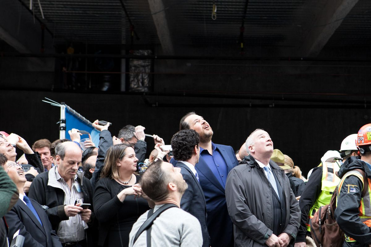 Benioff, press, and developers watch as the final beam ascends.