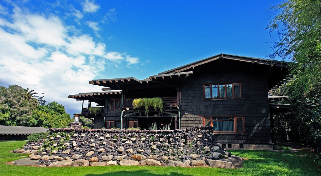 The exterior of the Gamble House. The facade is brown and there is a stone fence.