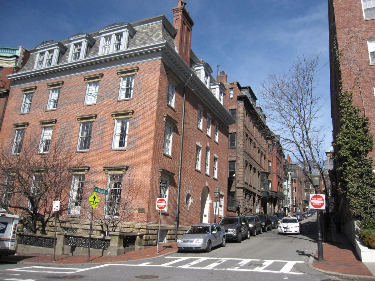 A four-story brick apartment building at a corner.