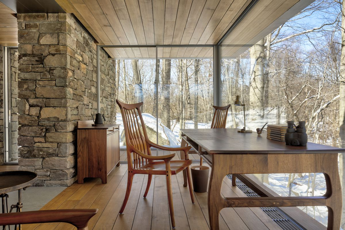 Writer's desk surrounded by windows and a stone wall.