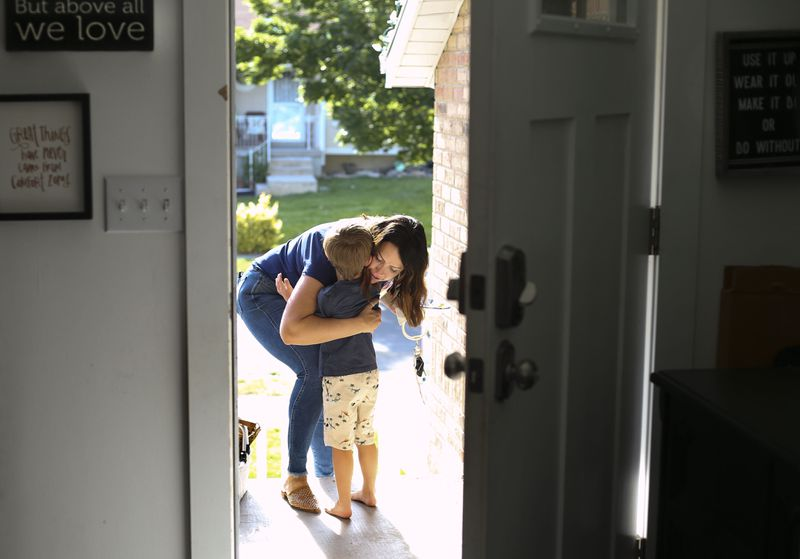 April Ethington gets a hug from her son, Nixon, as she heads off to work in Midvale on Thursday, June 4, 2020.