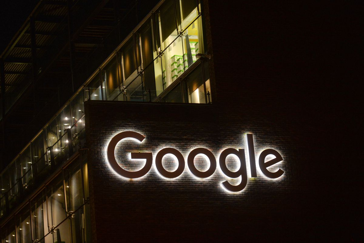 A glowing white Google logo on the side of a brick building.