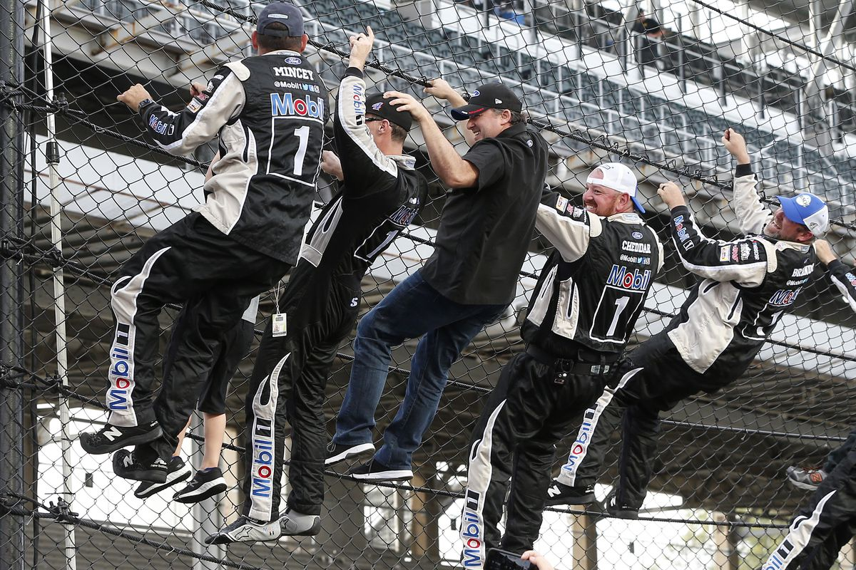 Team owner Tony Stewart and Kevin Harvick, driver of the #4 Mobil 1 Ford, climb the fence to celebrate winning the Monster Energy NASCAR Cup Series Big Machine Vodka 400 at the Brickyard at Indianapolis Motor Speedway on September 08, 2019 in Indianapolis, Indiana.