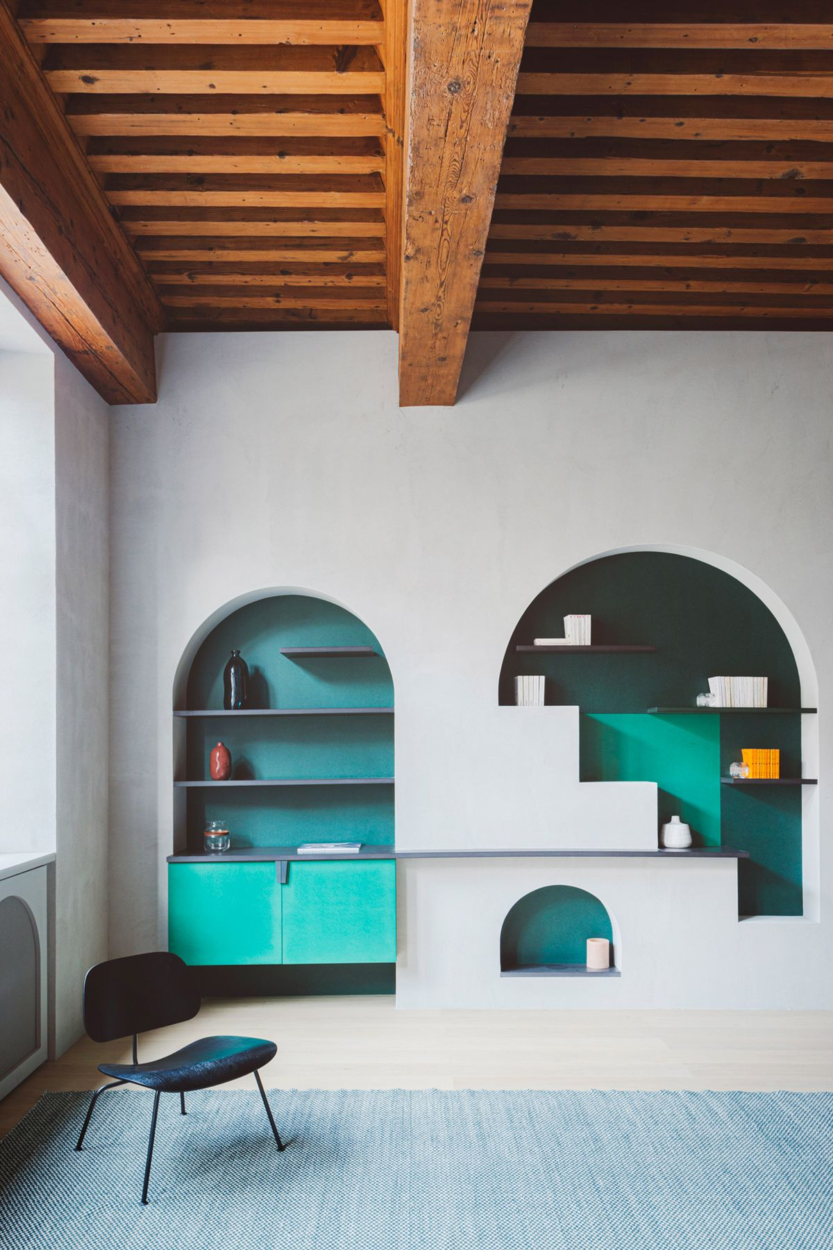 Arched shelving built into wall.