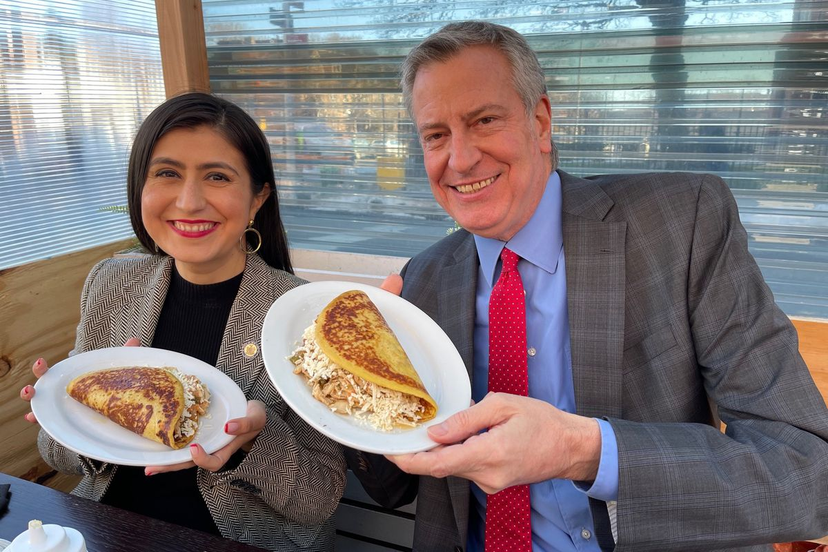 A man and a woman smile at the camera and hold up white plates containing one large arepa each