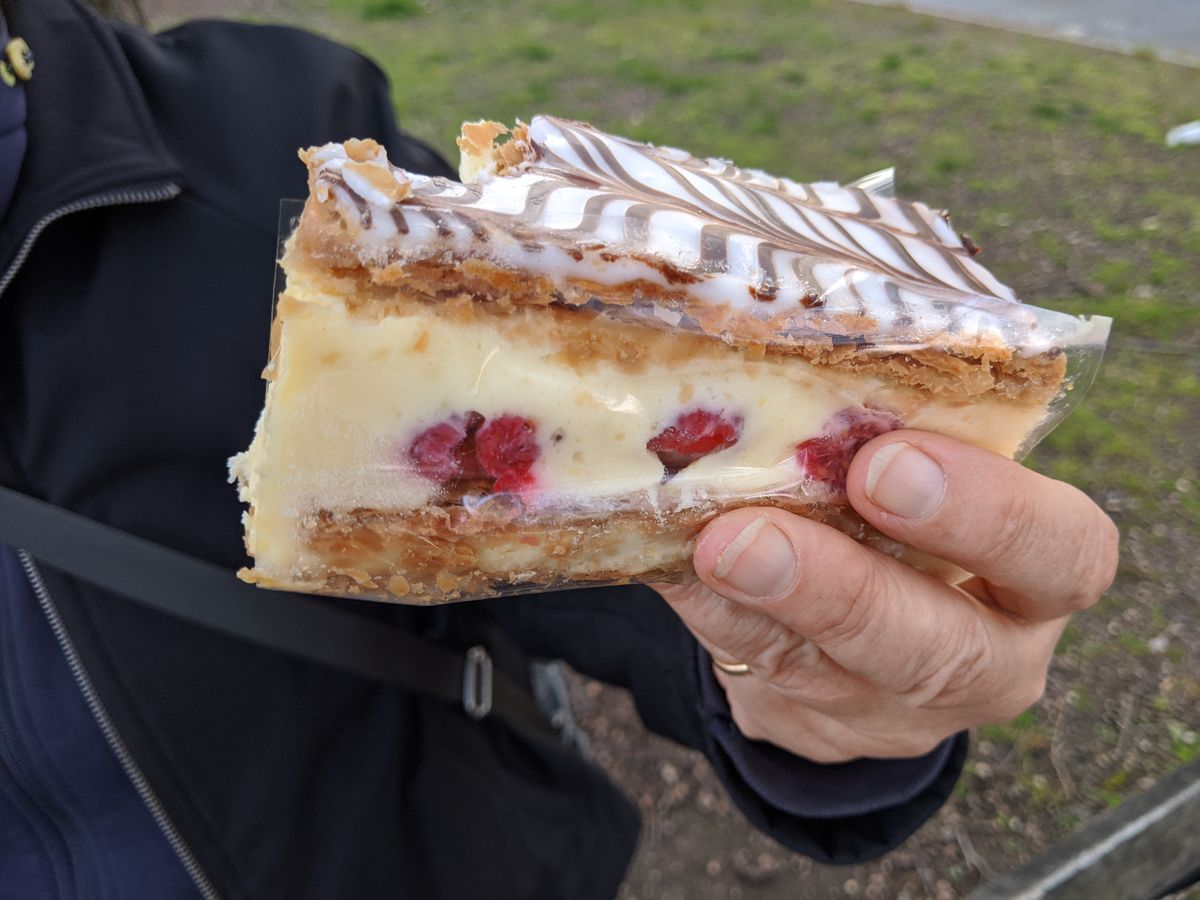 A hand holding a pastry filled with yellow cream in the center along with some raspberries
